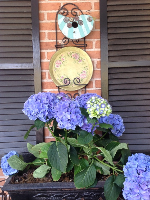 We hung a plate rack on the brick wall above a flower planter and have a decorative metal plate and a bird house as wall art