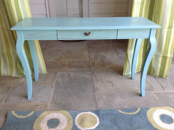Using a trash-picked console table to delienate the space, deal with an off center mudroom door, and keep an entry acess tonthe mudroom open. I painted the table blue like the rug and swapped out an ugly drawer knob with a cute bird one
