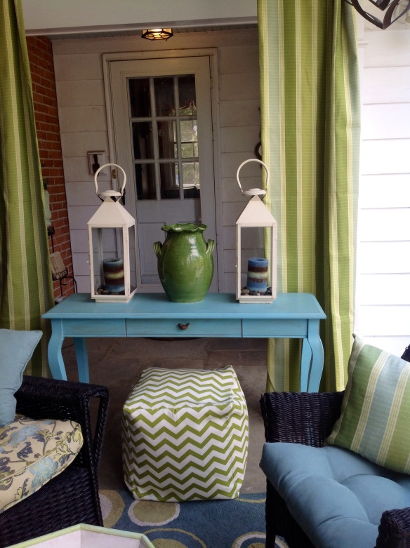 Accesorizing the console: 2 lanterns with blue candles on river rock, a large green pottery vase as sculpture and to block the mudroom door from view, and a chevron patterned bean bag ottoman(Tuesday Morning)