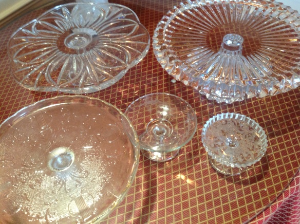 I select an assorted collection of pedestal glass cake stands and dishes of graduated sizes