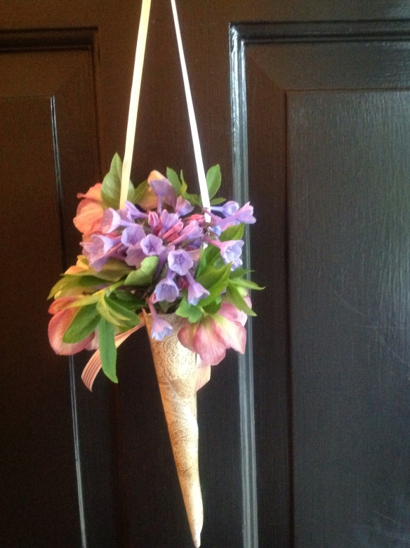 A simple bouquet of Virginia bluebells and hellebores in a paper cone