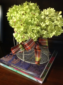 A trio of stems in a galvanized steel basket is a simple arrangement on a bookcase. A ribbon adds a punch of color.