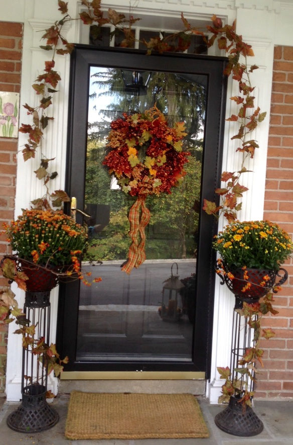It's all about the layering. The mums are placed in a wrought iron planter to elevate them. Bittersweet wine is woven at the base for another layer and the eye is drawn to the planter's height and pedestal detail by a garland cascading downwards. This same garland is repeated to frame the door and seasonal wreath.