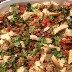 The browned sausage, vegetabkes, herbs and bread combined inthe baking dish.