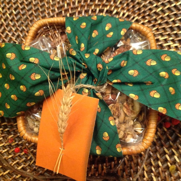 A darling basket with a cellophane packet of granola tied in a seasonal ribbon with a tag with a blade of wheat woven through 2 slits on a piece or recycled cardboard