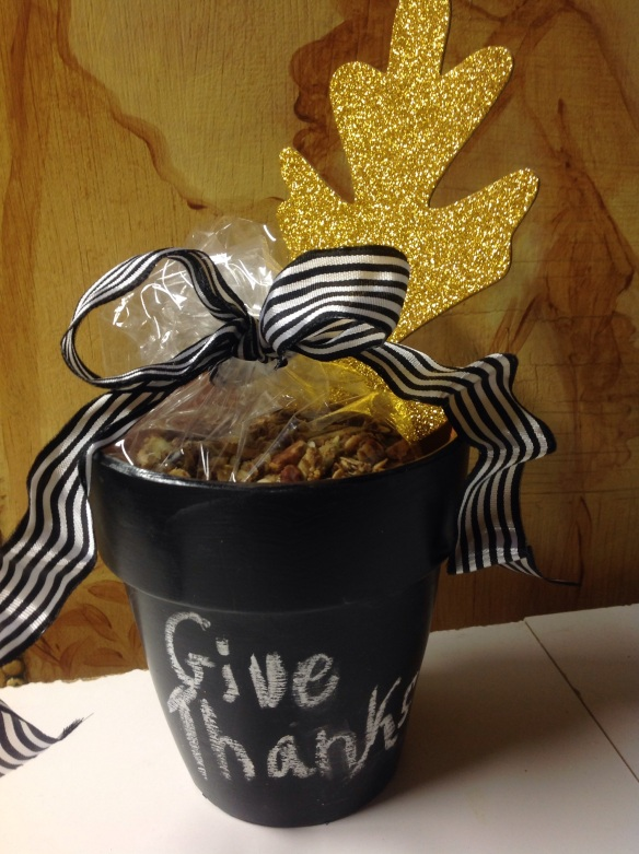 The most chic presentation of all.  A crisp black and white French ribbon ties a cellophane bag of granola and a glittery gold oak leaf (Michaels) is used as a tag in the planter.