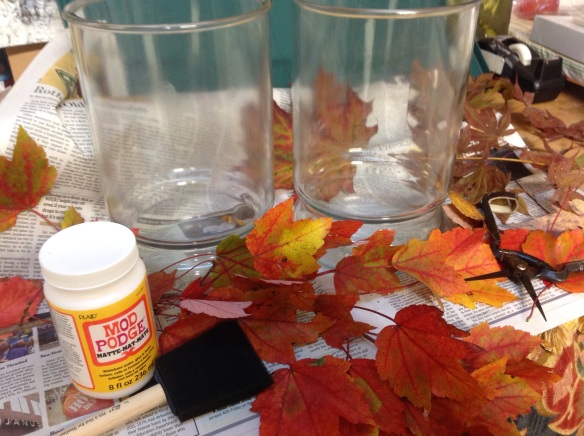 Supplies needed: clean glass vessel, leaves, Mod Podge, spong paint brush, newspaper, pruners to clip leaves free of stems
