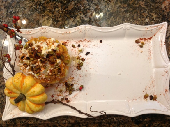 Setting up the presentation: the dip is scooped into a squash, the lid is leaned on the side for a pretty detail. A bittersweet vine snuggles next to the squash for a layering of seasonal detail. Paprika is sprinkled around the edges of the platter along with some of the feta and pistachio topping.