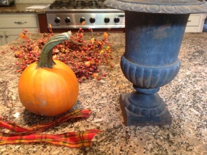 Materials: a garden urn, a sugar pumpkin, filler, a wreath, ribbon, bittersweet vine