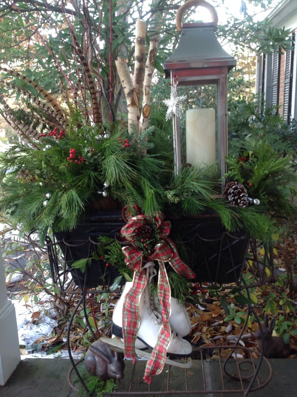 A winter planter showcases a tall lantern surrounded by natural greens, phesant feathers, red twig dogwood, skates, ribbon and a star ornament.