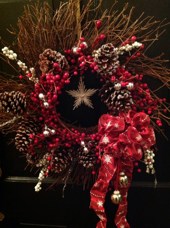 The wreath was created by wiring a red berry wreath over a tig one, adding glittery pinecones, a glitter star ornament, sleigh bells and a red ribbon bow with glittery silver snowflakes. This set the theme for the rest of the proch décor.