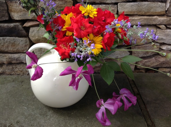 Smaller clematis can be cut on long sections of vines to cascade over a cottage arrangement in a pitcher.